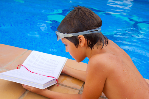 kid reading book near blue pool in summer day